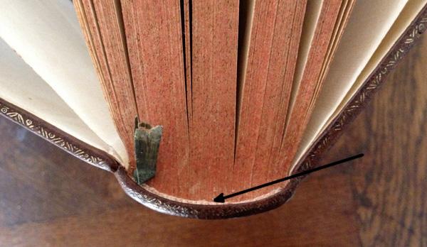 dos d'un livre ancien, bien collé au bloc-page. Pas de creux près de la tranchefile.